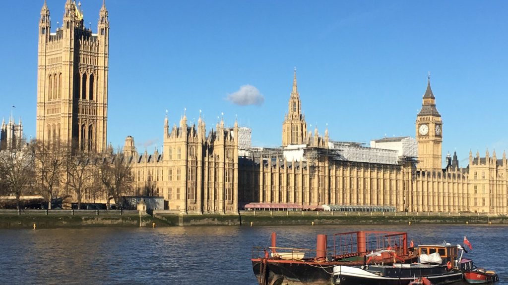 a large clock tower towering over the city of london with Palace of Westminster in the background