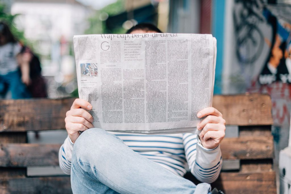 a person sitting on a bench reading a newspaper