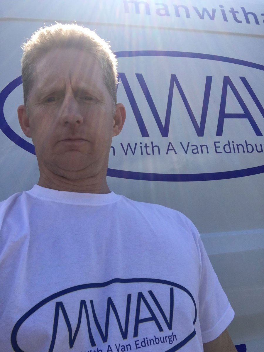 man with a van edinburgh in front of logo posing for the camera