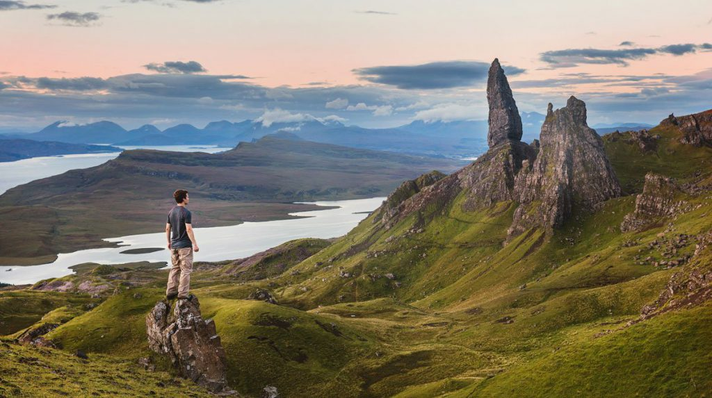 a man standing on a rocky hill with The Storr in the background